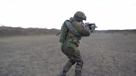 katonai : A soldier with a machine gun on a military firing range shooting at a target. Stock mozgókép