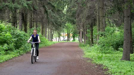 pneus : Woman riding a bike through a green forest Stock Footage