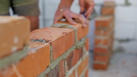 site : Work lays bricks on a construction site Stock Footage