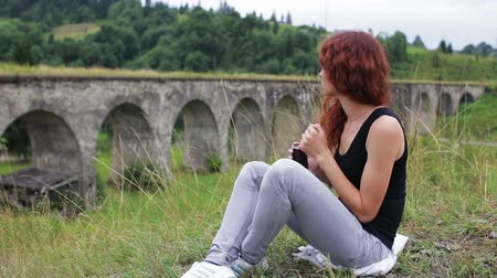 bridge man made structure : Girl dancing while sitting near the old viaduct in the mountains