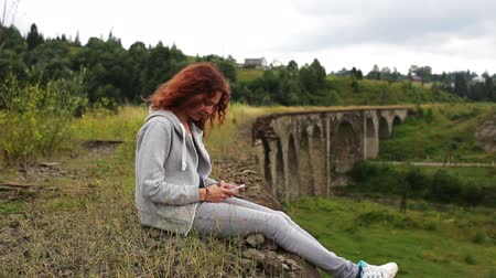 bridge man made structure : The girl writes sms sitting near the old viaduct in the mountains Stock Footage
