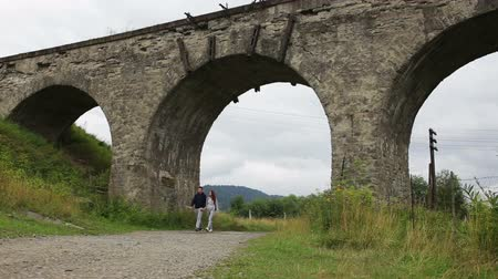 bridge man made structure : Happy couple walking along the road under the old viaduct