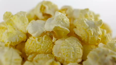 estalo : Salt popcorn in box on white background, rotation, very close up Vídeos