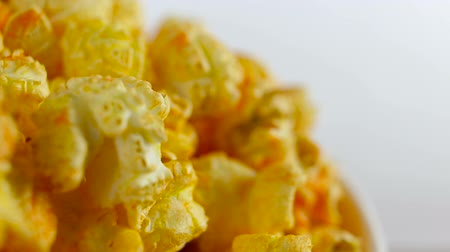 full bucket : Cheese popcorn in box on white background, rotation, very close up