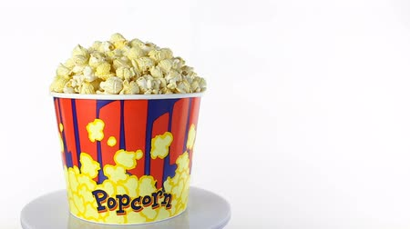 saborear : Salty popcorn rotates on a white background. Wide shot