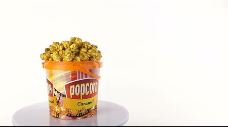 попкорн : Caramel popcorn rotates on a white background. Wide shot
