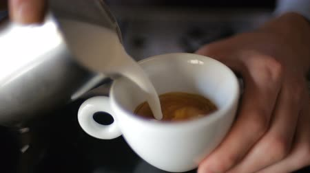 coffer : frothed milk is poured into a cup of coffee. cappuccino preparation