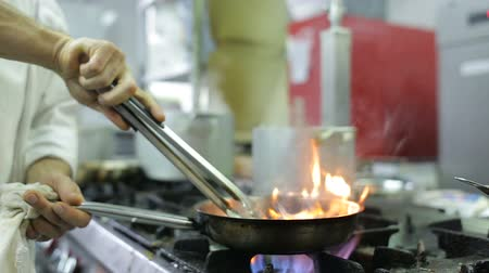 serpenyő : Chef in a kitchen cooking flambe style Stock mozgókép
