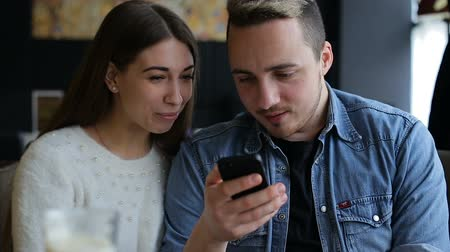 olhares : Young happy couple with smartphone in cafe