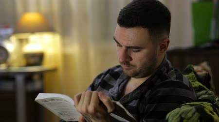 poezja : Man reading book sitting on sofa at night at home