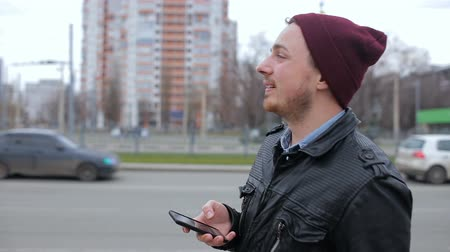 gaining : Attractive man looking at mobile phone while waiting in city bus stop