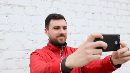 борода : Young cute guy doing selfie near white brick wall Стоковые видеозаписи