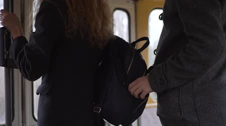 property theft : Pickpocket stealing phone from a womans handbag in tram or bus