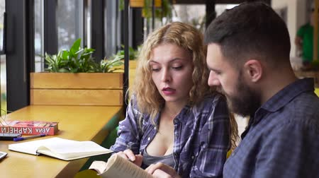 magyarázza : PAN of young woman explains to a young man a complex material in a book sitting in a cafe