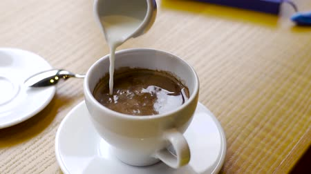 caffe : Frothed milk is poured into a cup of coffee. cappuccino preparation