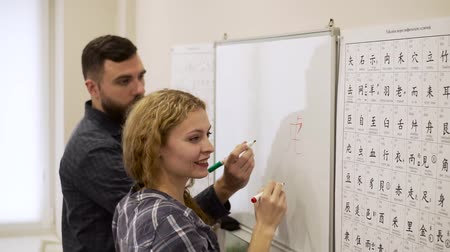 японский рисунок : Medium shot of young man helps a girl learn Chinese characters in the office