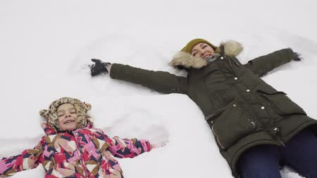 snow angel : Little girl and her mother makes a snow angel