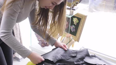 roupagem : Young beautiful woman chooses the fabric in a textile shop