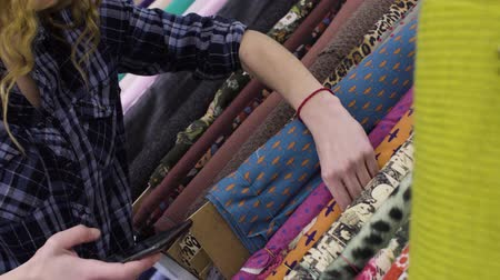 samples of fabric : Young beautiful woman chooses the fabric in a textile shop