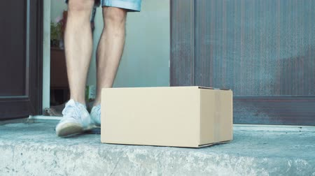 felpudo : A man picks up a package from outside his front door