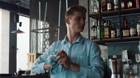 towel white : Bartender wiping glasses behind the bar Stock Footage