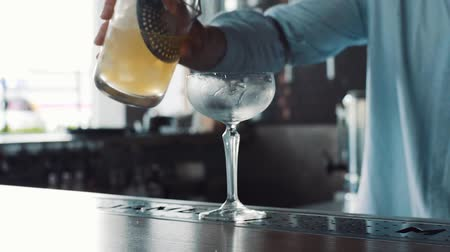 tincture : Closeup of bartender pouring drink into the glass