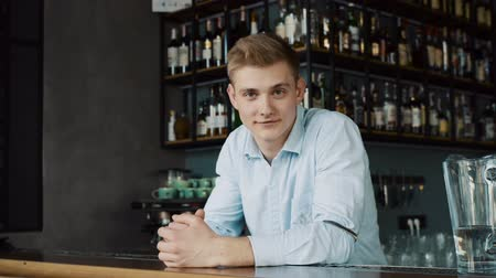 caffe : Portrait of a happy young bartender behind the counter