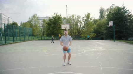 camera rotation : Front view of basketball player practicing free throws outdoors Stock Footage