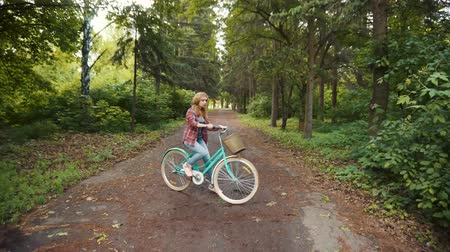 camera rotation : Happy female rides a bike through the park and stops in front of the camera Stock Footage