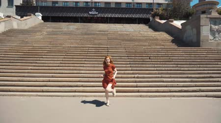 dans : City portrait of a girl in a dress dances against a backdrop of stairs