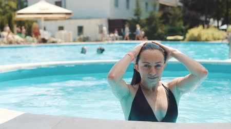 amigo : Beautiful young woman emerges from the pool