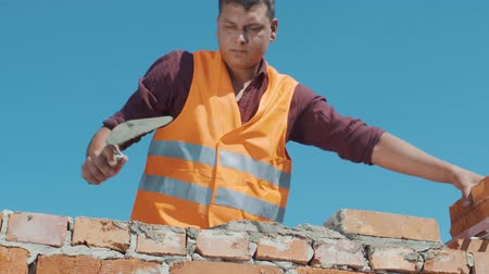 pracownik budowlany : Bricklayer build wall on a blue sky background Wideo