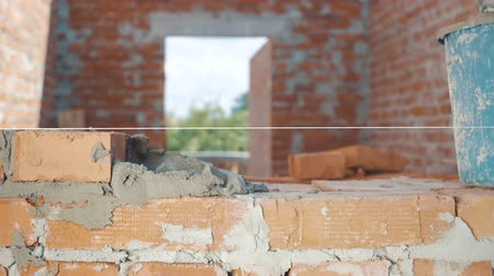 cálcio : Close-up shot of Bricklayer builds wall into house