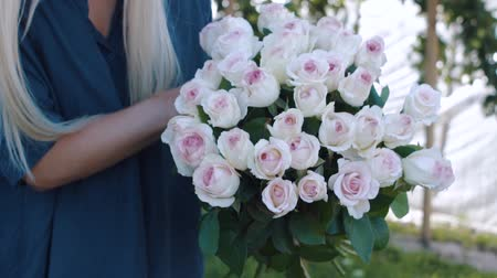florista : Woman makes a bouquet in the rose garden