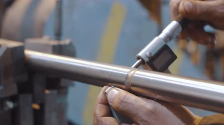 The workers hands are measured using a metal ruler, the diameter of tube Stock Footage