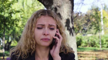 lágrima : girl crying speaking on the phone sitting on a bench in the park Stock Footage
