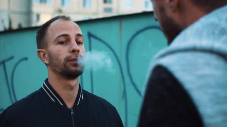ansiedade : Men stand in the stret talk and smoke