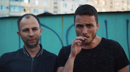 крупные планы : Two men smoke cigarettes in the ghetto and look into the camera