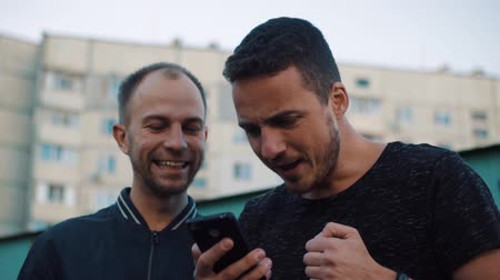 Two men emotionally happy after the news in the phone