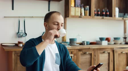 Man using phone while having cup of coffee in kitchen at home 4k 影像素材