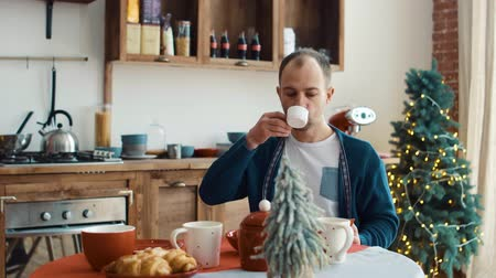 Man having cup of coffee in kitchen at home 4k 影像素材