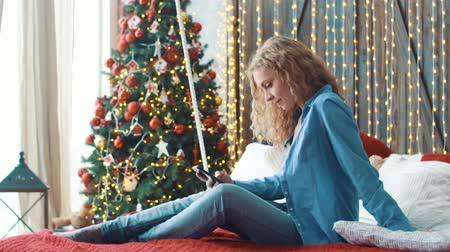 Attractive blonde girl sitting on a sofa at home and texting on her phone Stock Footage