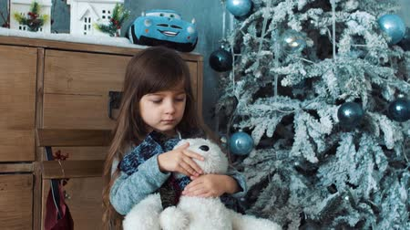 Girl is sad and hug white teddy bear