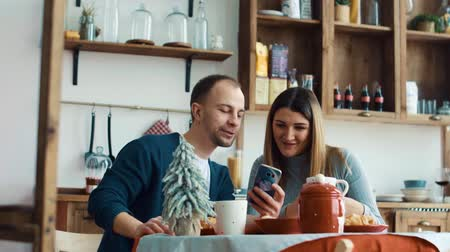 a böngésző : Pregnant wife and husband have breakfast in the kitchen with a smartphone