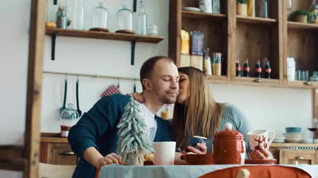 Pregnant wife and husband have breakfast in the kitchen with a smartphone