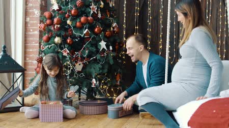 sabah : The little girl, dad and pregnant mom near the Christmas tree Stok Video