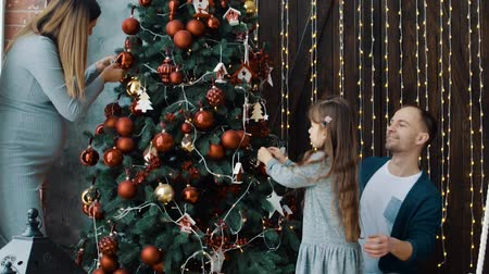 The little girl, dad and pregnant mom near the Christmas tree Stock Footage