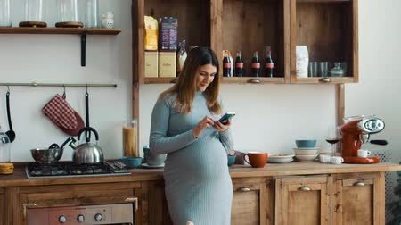 Pregnant woman in the kitchen uses smartphone Vídeos