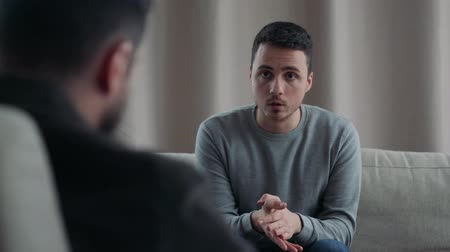 counselling : A young man tells a psychologist that he cares Stock Footage