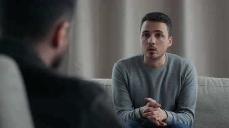 доктор : Young man talking to his therapist at therapy session Стоковые видеозаписи